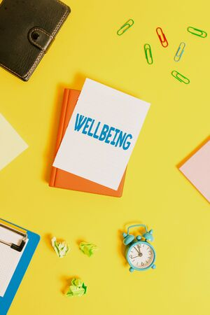 Text sign showing Wellbeing. Business photo showcasing A good or satisfactory condition of existence including health Pile of empty papers with copy space on the table Zdjęcie Seryjne
