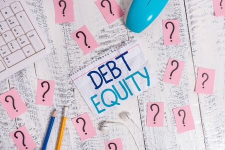 Writing note showing Debt Equity. Business concept for dividing companys total liabilities by its stockholders Writing tools and scribbled paper on top of the wooden table