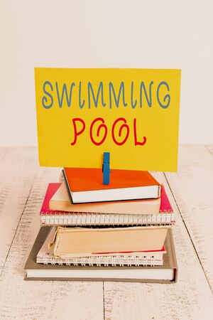 Conceptual hand writing showing Swimming Pool. Concept meaning Structure designed to hold water for leisure activities pile stacked books notebook pin color reminder white wooden