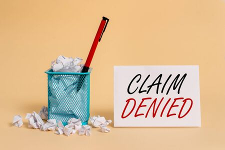 Text sign showing Claim Denied. Business photo showcasing Requested reimbursement payment for bill has been refused crumpled paper trash and stationary with note paper placed in the trash can