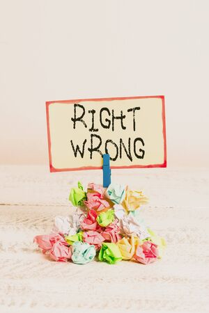 Writing note showing Right Wrong. Business concept for choose between two decisions correct and bad one to make Reminder pile colored crumpled paper clothespin wooden space