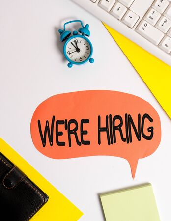 Word writing text We Re Hiring. Business photo showcasing Advertising Employment Workforce Placement New Job Flat lay with copy space on bubble paper clock and paper clips Zdjęcie Seryjne