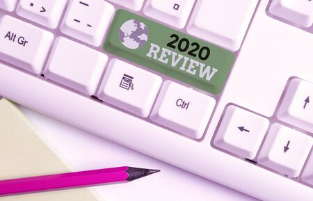 Writing note showing 2020 Review. Business concept for seeing important events or actions that made previous year White pc keyboard with note paper above the white background Фото со стока