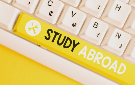 Conceptual hand writing showing Study Abroad. Concept meaning Pursuing educational opportunities in a foreign country White pc keyboard with note paper above the white background