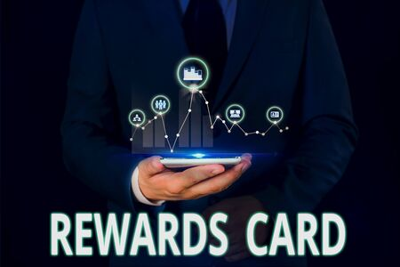 Text sign showing Rewards Card. Business photo showcasing Help earn cash points miles from everyday purchase Incentives Male human wear formal work suit presenting presentation using smart device Stock Photo
