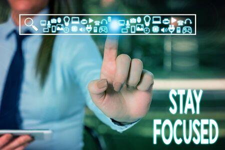Handwriting text writing Stay Focused. Conceptual photo Be attentive Concentrate Prioritize the task Avoid distractions Woman wear formal work suit presenting presentation using smart device