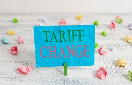 Word writing text Tariff Change. Business photo showcasing Amendment of Import Export taxes for goods and services Green clothespin white wood background colored paper reminder office supply