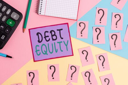 Handwriting text Debt Equity. Conceptual photo dividing companys total liabilities by its stockholders Mathematics stuff and writing equipment above pastel colours background