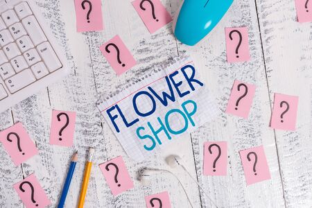 Writing note showing Flower Shop. Business concept for where cut flowers are sold with decorations for gifts Writing tools and scribbled paper on top of the wooden table