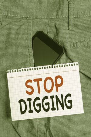 Handwriting text Stop Digging. Conceptual photo Prevent Illegal excavation quarry Environment Conservation Smartphone device inside formal work trousers front pocket near note paper Фото со стока