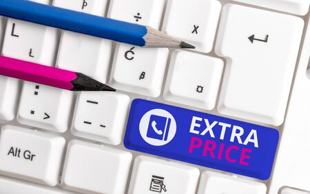 Writing note showing Extra Price. Business concept for extra price definition beyond the ordinary large degree White pc keyboard with note paper above the white background 写真素材