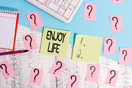 Conceptual hand writing showing Enjoy Life. Concept meaning Any thing, place,food or demonstrating, that makes you relax and happy Writing tools and scribbled paper on top of the wooden table