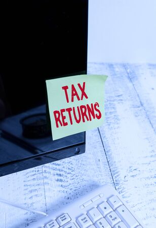 Word writing text Tax Returns. Business photo showcasing Tax payer financial information Tax Liability and Payment report Notation paper taped to black computer monitor screen near white keyboard
