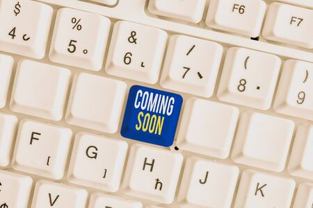 Conceptual hand writing showing Coming Soon. Concept meaning something is going to happen in really short time of period White pc keyboard with note paper above the white background Фото со стока