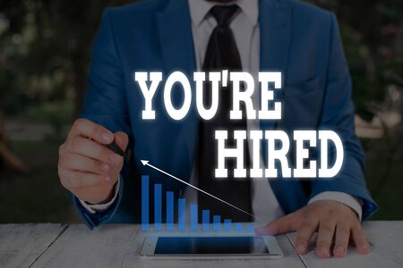 Handwriting text writing You Re Hired. Conceptual photo New Job Employed Newbie Enlisted Accepted Recruited Male human wear formal work suit presenting presentation using smart device
