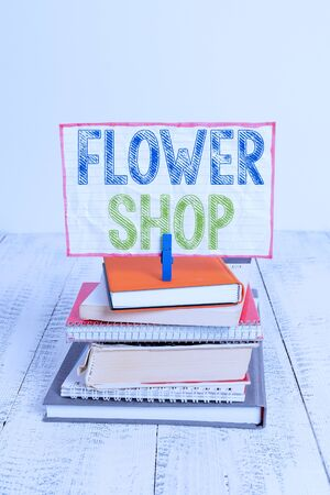 Word writing text Flower Shop. Business photo showcasing where cut flowers are sold with decorations for gifts pile stacked books notebook pin clothespin colored reminder white wooden