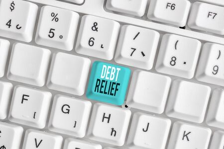 Writing note showing Debt Relief. Business concept for partial or total remission of it especially those by countries White pc keyboard with note paper above the white background Zdjęcie Seryjne