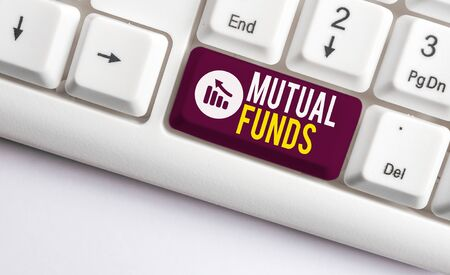Writing note showing Mutual Funds. Business concept for An investment program funded by shareholders Individual Stocks White pc keyboard with note paper above the white background