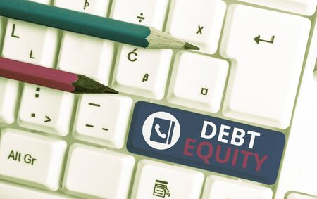 Writing note showing Debt Equity. Business concept for dividing companys total liabilities by its stockholders White pc keyboard with note paper above the white background