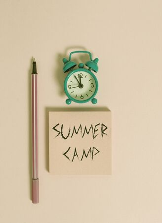 Text sign showing Summer Camp. Business photo text Supervised program for kids and teenagers during summertime. Metal vintage alarm clock wakeup blank notepad marker colored background