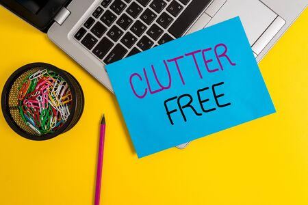 Word writing text Clutter Free. Business photo showcasing Well organized and arranged Tidy All things in right places Trendy metallic laptop small paper sheet pencil clips colored background Фото со стока
