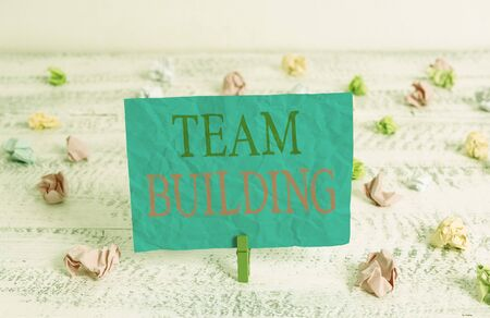 Word writing text Team Building. Business photo showcasing Types of activities used to enhance social relations Green clothespin white wood background colored paper reminder office supply