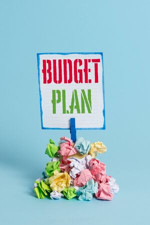 Word writing text Budget Plan. Business photo showcasing financial schedule for a defined period of time usually year Reminder pile colored crumpled paper clothespin reminder blue background