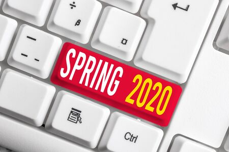 Handwriting text writing Spring 2020. Conceptual photo time of year where flowers rise following winter season White pc keyboard with empty note paper above white background key copy space