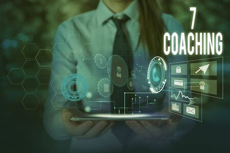 Writing note showing 7 Coaching. Business concept for Refers to a number of figures regarding business to be succesful Woman wear formal work suit presenting presentation using smart device Stok Fotoğraf