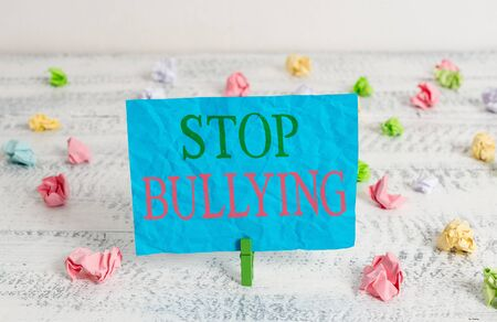 Word writing text Stop Bullying. Business photo showcasing Fight and Eliminate this Aggressive Unacceptable Behavior Green clothespin white wood background colored paper reminder office supply