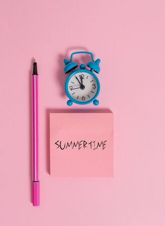Text sign showing Summertime. Business photo text Longer daylight Tropical season Beach activities Vacation Metal vintage alarm clock wakeup blank notepad marker colored background