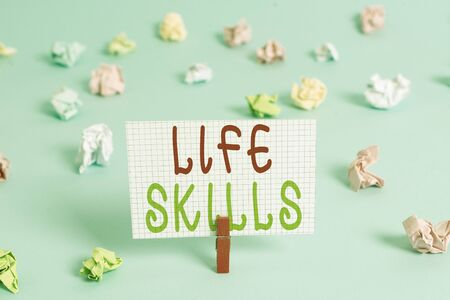 Conceptual hand writing showing Life Skills. Concept meaning that is necessary or desirable full participation in everyday Colored clothespin rectangle shaped paper blue background Фото со стока