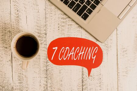 Word writing text 7 Coaching. Business photo showcasing Refers to a number of figures regarding business to be succesful Trendy metallic open laptop speech bubble vintage wooden table coffee cup