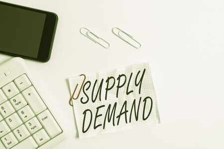 Text sign showing Supply Deanalysisd. Business photo showcasing Relationship between the amounts available and wanted White pc keyboard with empty note paper above white background and mobile phone Reklamní fotografie