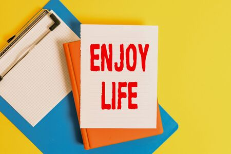 Word writing text Enjoy Life. Business photo showcasing Any thing, place,food or demonstrating, that makes you relax and happy Pile of empty papers with copy space on the table
