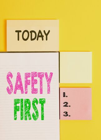 Word writing text Safety First. Business photo showcasing Avoid any unnecessary risk Live Safely Be Careful Pay attention Colored empty papers with copy space on the yellow background table