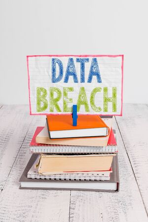 Word writing text Data Breach. Business photo showcasing security incident where sensitive protected information copied pile stacked books notebook pin clothespin colored reminder white wooden