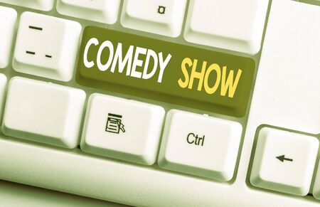 Conceptual hand writing showing Comedy Show. Concept meaning Funny program Humorous Amusing medium of Entertainment White pc keyboard with note paper above the white background