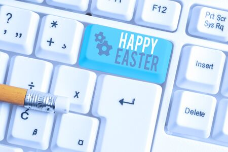 Writing note showing Happy Easter. Business concept for Christian feast commemorating the resurrection of Jesus White pc keyboard with note paper above the white background Фото со стока