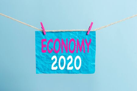 Writing note showing Economy 2020. Business concept for State of wealth and resources of a country in upcoming year Clothesline clothespin rectangle shaped paper reminder white wood desk