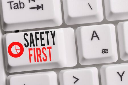 Conceptual hand writing showing Safety First. Concept meaning Avoid any unnecessary risk Live Safely Be Careful Pay attention Keyboard with note paper on white background key copy space