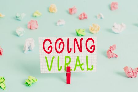 Conceptual hand writing showing Going Viral. Concept meaning image video or link that spreads rapidly through population Colored clothespin rectangle shaped paper blue background Фото со стока