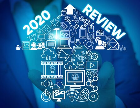 Writing note showing 2020 Review. Business concept for seeing important events or actions that made previous year Male wear formal work suit presenting presentation smart device 스톡 콘텐츠