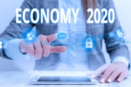 Writing note showing Economy 2020. Business concept for State of wealth and resources of a country in upcoming year Female human wear formal work suit presenting smart device 스톡 콘텐츠