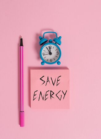 Text sign showing Save Energy. Business photo text decreasing the amount of power used achieving a similar outcome Metal vintage alarm clock wakeup blank notepad marker colored background