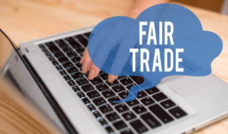 Conceptual hand writing showing Fair Trade. Concept meaning Small increase by a analysisufacturer what they paid to a producer woman with laptop smartphone and office supplies technology
