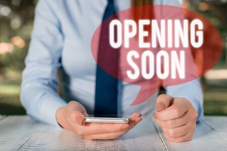 Writing note showing Opening Soon. Business concept for Going to be available or accessible in public anytime shortly Female business person sitting by table and holding mobile phone