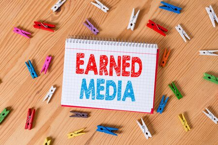 Conceptual hand writing showing Earned Media. Concept meaning Publicity gained through promotional efforts by multimedia Colored crumpled papers wooden floor background clothespin Фото со стока