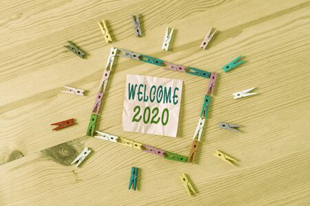 Text sign showing Welcome 2020. Business photo showcasing New Year Celebration Motivation to Start Cheers Congratulations Colored clothespin papers empty reminder wooden floor background office