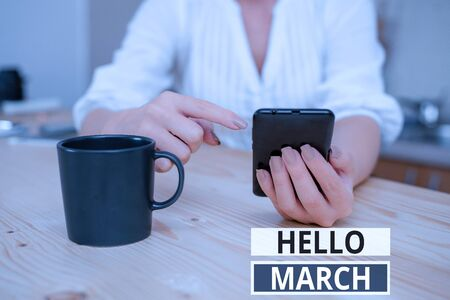 Text sign showing Hello March. Business photo showcasing musical composition usually in duple or quadruple with beat woman using smartphone office supplies technological devices inside home